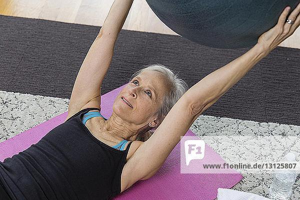 Ältere Frau hält Fitnessball in der Hand  während sie zu Hause auf einer Trainingsmatte liegt