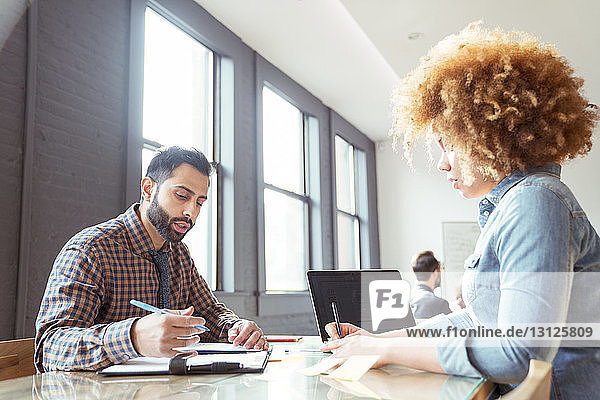 Geschäftsleute  die arbeiten  während sie im Büro am Tisch sitzen