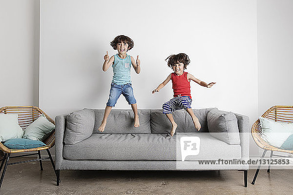 Portrait of happy brothers jumping on sofa against wall at home
