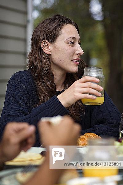 Junge Frau schaut weg  während sie während des Mittagessens Orangensaft trinkt