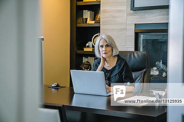 Porträt einer Geschäftsfrau  die am Laptop-Computer am Schreibtisch im Büro arbeitet  durch die Tür gesehen