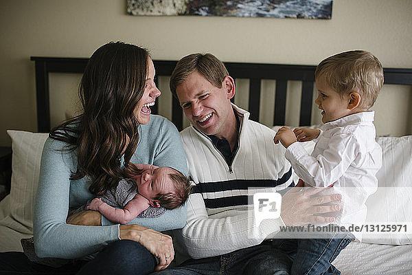 Glückliche Eltern  deren Söhne zu Hause im Bett sitzen