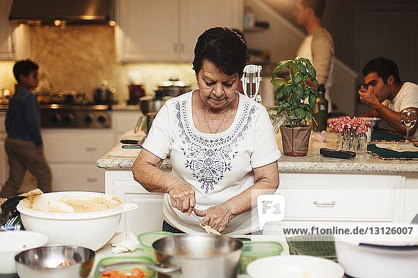 Ältere Frau kocht Essen  während Söhne und Enkel im Hintergrund in der Küche stehen