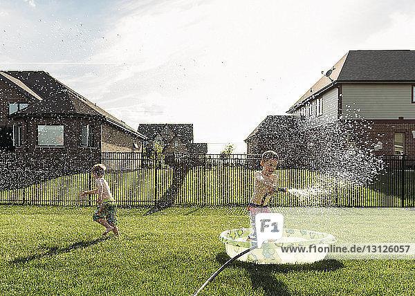 Boy running while brother spraying water at backyard