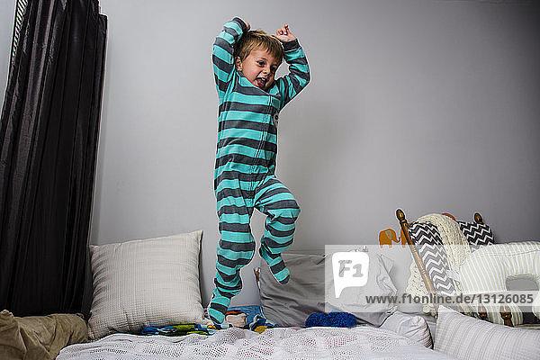 Verspielter Junge  der zu Hause auf dem Bett hüpft