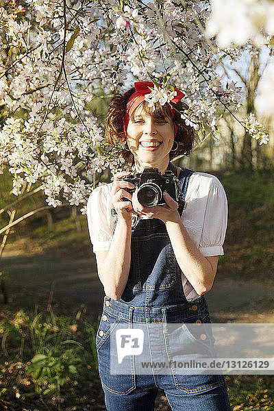 Portrait of happy woman photographing through camera while standing in park