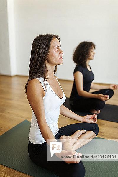 Freundinnen meditieren beim Sitzen im Yoga-Kurs