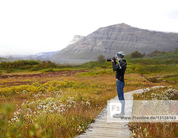 Side view of hiker photographing with camera while standing on boardwalk against mountains