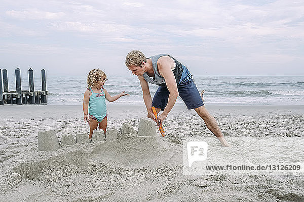 Father making sand castle by daughter at Cape May Beach against sky