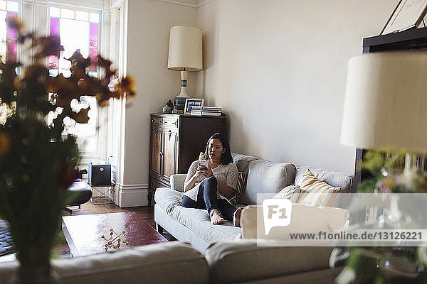 Woman using mobile phone while relaxing on sofa at home