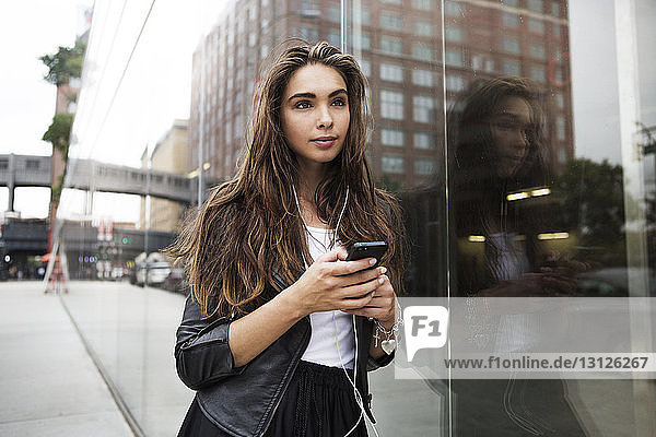 Beautiful woman listening music while standing by glass window