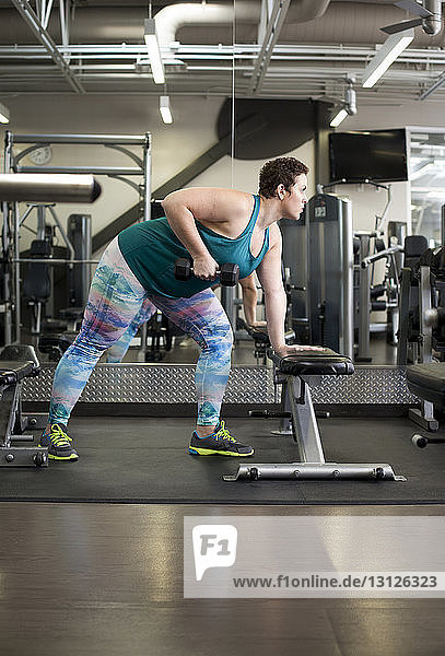 Full length of woman lifting dumbbell while exercising in gym