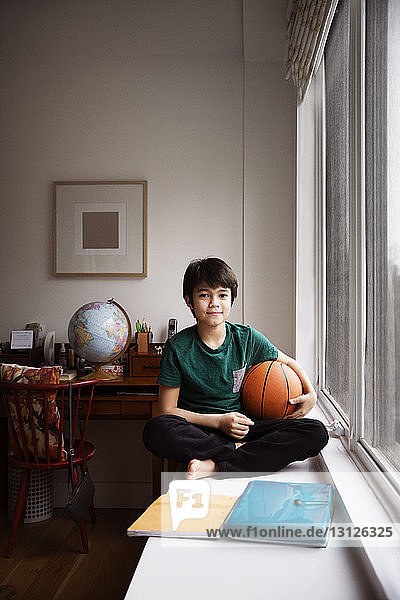 Portrait of boy holding ball and sitting on table by window at home