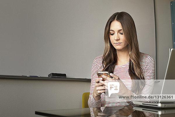 Schöne Geschäftsfrau benutzt Smartphone im Kreativbüro