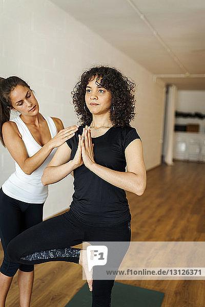 Yogalehrerin unterstützt Frau beim Üben der Baumposition im Yogastudio