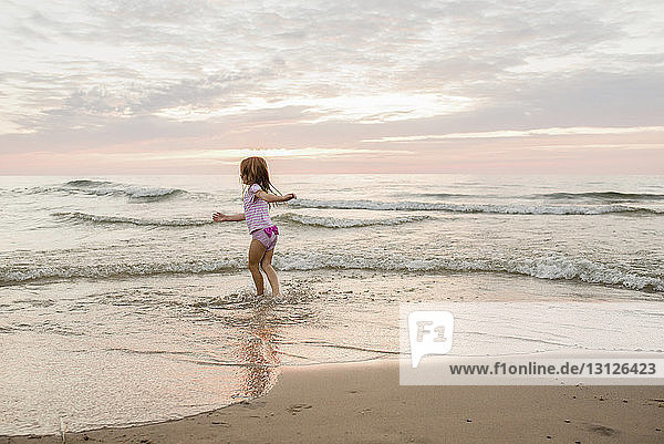 Carefree girl playing on shore at beach against cloudy sky during sunset