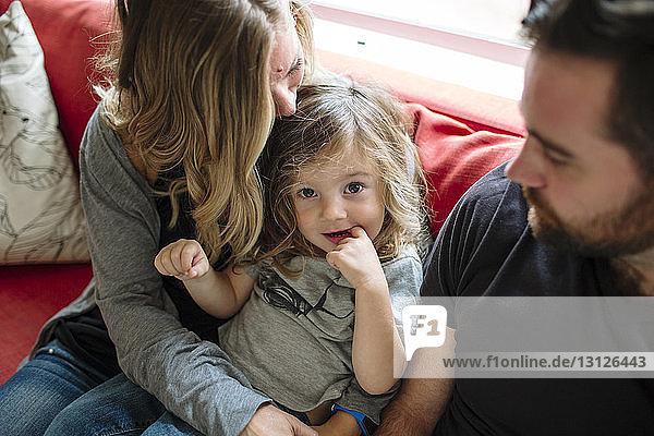 Hochwinkelporträt einer niedlichen Tochter mit dem Finger im Mund sitzend von Vater und Mutter zu Hause auf dem Sofa