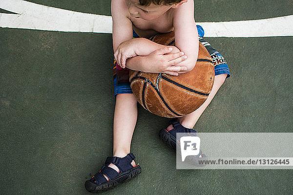 Schrägaufnahme eines Jungen  der einen Basketball hält  während er auf dem Platz sitzt