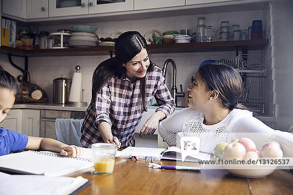 Mother talking to daughter studying at table in kitchen