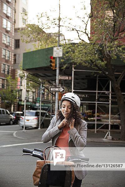 Geschäftsfrau  die einen Helm trägt  während sie beim Fahrrad steht