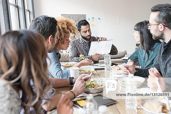Geschäftsmann zeigt Kollegen Dokumente beim Essen am Tisch