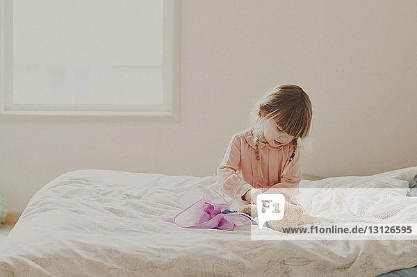 Mädchen spielt mit Teddybär auf dem Bett
