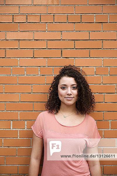 Porträt einer selbstbewussten Geschäftsfrau  die an einer Ziegelmauer steht