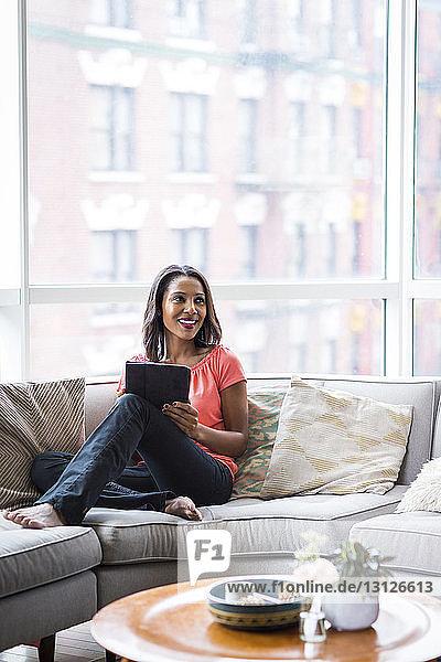 Glückliche Frau schaut weg  während sie zu Hause einen Tablet-Computer auf dem Sofa gegen das Fenster hält