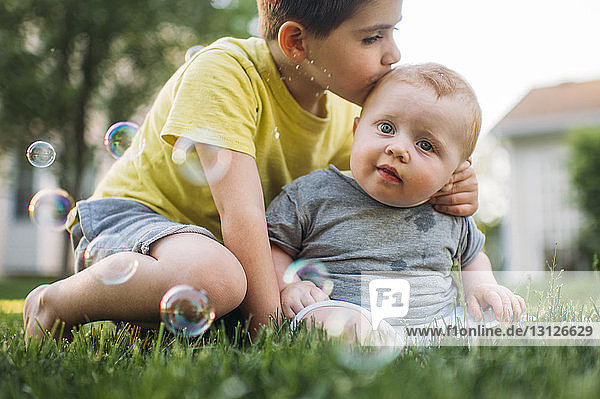 Boy kissing brother while sitting on grassy field at back yard