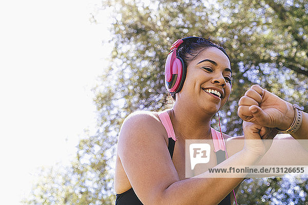 Low angle view of happy woman looking at fitness tracker while listening music at park