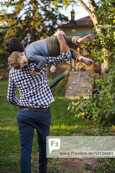 Rear view of playful father carrying son while walking on grassy field in yard during sunset