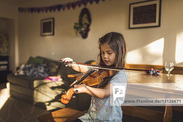 Mädchen spielt Geige  während sie zu Hause am Holztisch sitzt