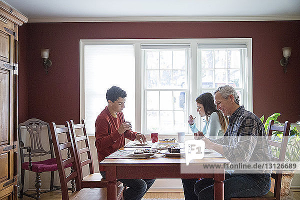 Happy family eating breakfast at table in home