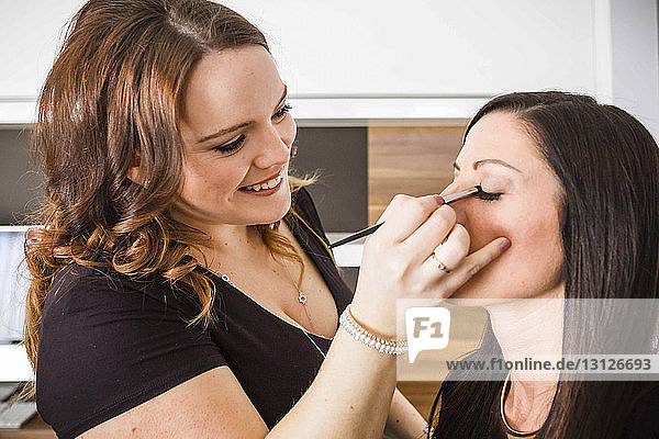 Beautician applying eyeshadow to woman