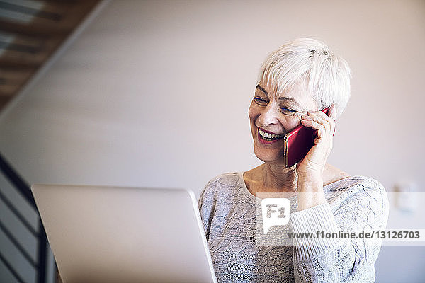 Happy senior woman talking on mobile phone while using laptop at home