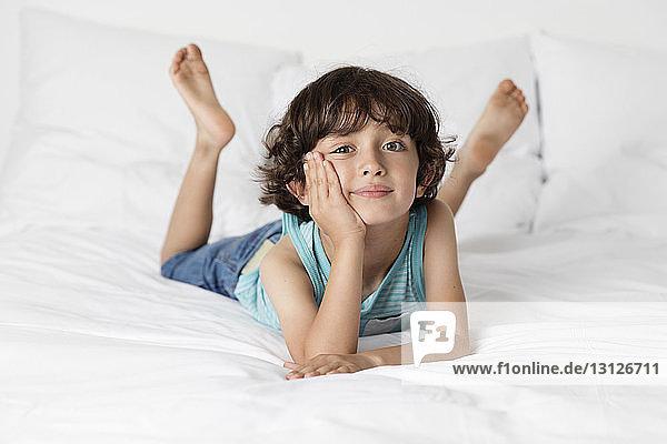 Porträt eines süßen Jungen  der sich zu Hause auf dem Bett ausruht