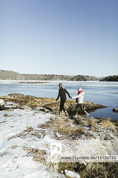 Freundinnen am Seeufer gegen klaren Himmel im Park im Winter