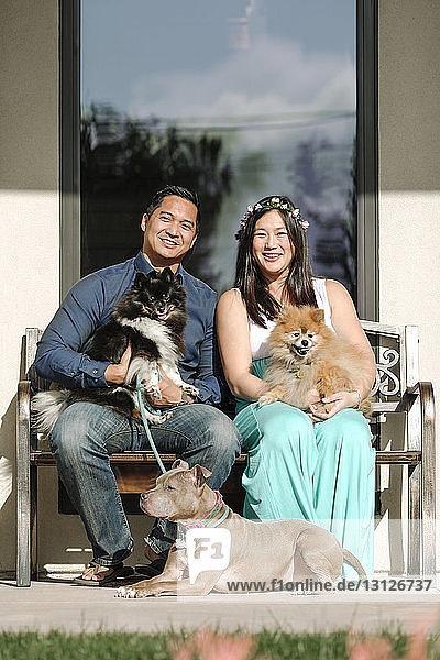 Portrait of confident smiling couple with dogs sitting on bench against house