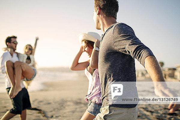 Fröhliche Paare genießen am Strand Fröhliche Paare genießen am Strand