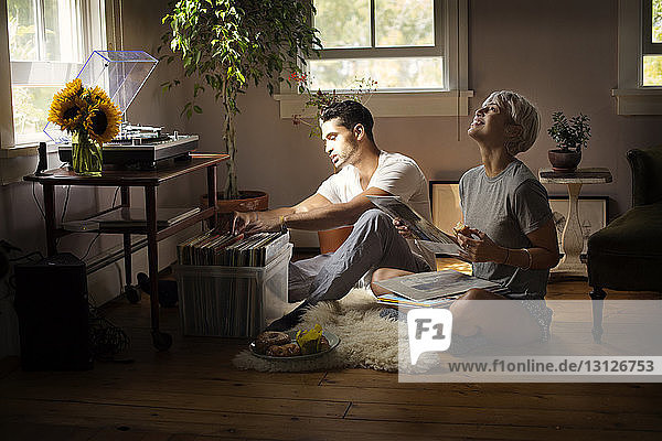 Happy young couple choosing vinyl record at home