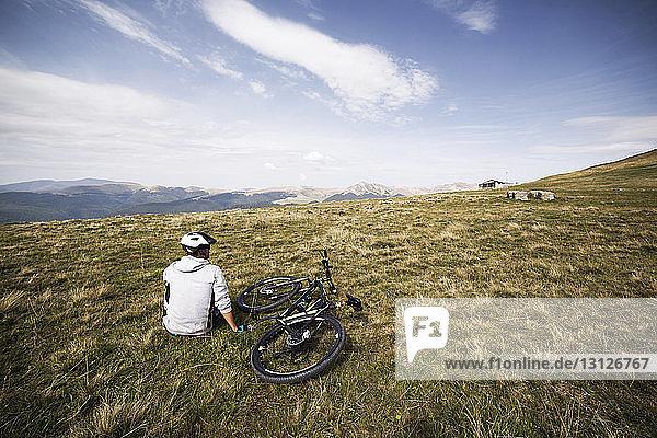 Rear view of mountain biker sitting on grass field against sky