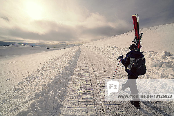 Rückansicht eines Mannes mit Skiern beim Gehen auf verschneitem Feld