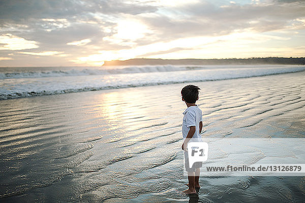 Side view of boy standing at beach against cloudy sky during sunset