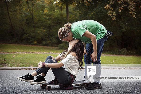 Mann küsst Frau  die auf einem Skateboard auf der Straße sitzt