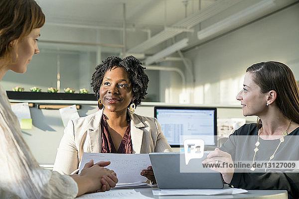 Lächelnde Geschäftsfrauen diskutieren über Tablet-Computer  während sie im Büro sitzen