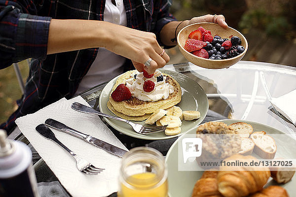 Midsection of young woman garnishing pancakes with strawberries and whipped cream