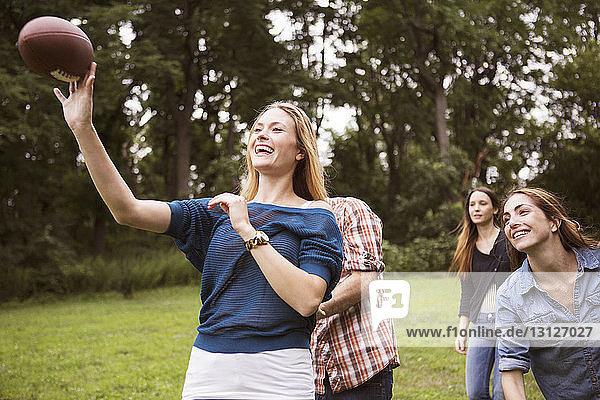 Spielerische Frau wirft Fussball  während Freunde auf dem Feld hinterherlaufen