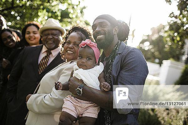 Porträt einer glücklichen Familie  die im Park gegen den Himmel steht