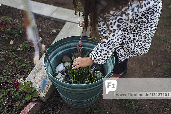 Low section of girl touching plant in yard