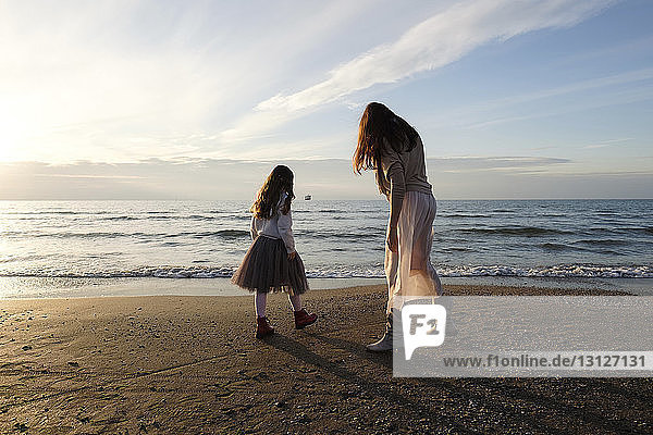 Mother with daughter standing at beach against sky during sunset